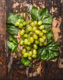 Fresh bright grapes on a branch with leaves on dark wooden background, top view. Fresh bright grapes on branch with leaves on dark wooden background, top view royalty free stock images
