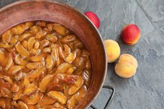 Homemade marmalade or jam processing from apricotes or peaches stock photo