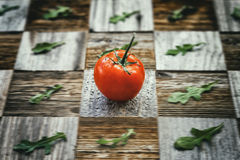 Fresh bright tomato, basil leaves on aged vintage surface mosaik board with pieces, different breeds as chess board. Fresh bright tomato with water drops, basil Royalty Free Stock Photography