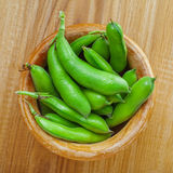 Fresh broad beans. Bowl of fresh podded broad beans on a wooden table. Healthy organic food Stock Photo
