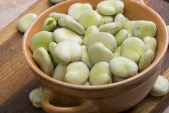 Fresh broad beans in bowl. On wooden board Royalty Free Stock Image