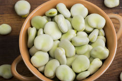 Fresh broad beans in bowl. On wooden board Stock Image