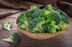 Fresh broccoli in basket on wooden table Royalty Free Stock Photography