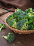 Fresh broccoli in basket on wooden table Stock Image