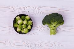 Fresh broccoli, Brussels sprouts in a bowl on a white wooden table - ecological products, healthy food. Flat lay.  Stock Photo