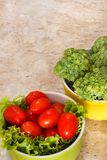 Fresh broccoli, cherry tomatoes in bowls. Fresh broccoli, tomatoes in green and yellow bowls Royalty Free Stock Photo