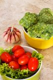 Fresh broccoli, cherry tomatoes and garlic. Fresh broccoli, tomatoes in green and yellow bowls with garlic Stock Images