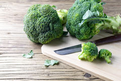 Fresh broccoli on a cutting board and knife. Closeup Stock Images