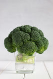 Fresh broccoli in glass of water on the white wooden table. Royalty Free Stock Photos