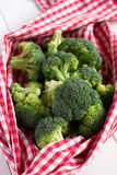 Fresh broccoli in kitchen towel on the white wooden table. Stock Images