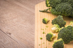 Fresh broccoli and knife on wooden table close up Royalty Free Stock Photo
