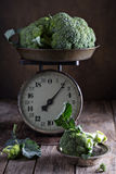 Fresh broccoli on old kitchen scales Royalty Free Stock Images