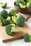 Fresh broccoli scattered on wooden table. Stock Images