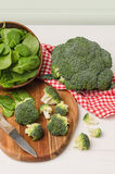 Fresh broccoli with spinach on wooden table close up Stock Photos