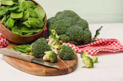Fresh broccoli with spinach on wooden table close up Stock Photo