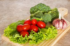 Fresh broccoli, tomatoes and garlic on wooden board. Fresh broccoli, cherry tomatoes and garlic on wooden board on table Royalty Free Stock Photos