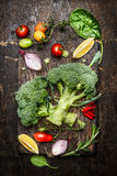 Fresh broccoli and vegetables ingredients and seasoning for tasty vegetarian cooking on rustic wooden background, top view Stock Image