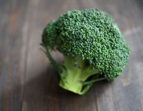 Fresh broccoli on the wooden table. Fresh green broccoli on the wooden table, closeup Stock Image