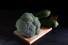Fresh broccoli and zucchini on a cutting board on a black background, rustic style, dark key. Healthy food stock image