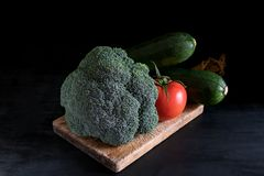 Fresh broccoli, zucchini and one tomato on a cutting board on a black background, rustic style, dark key stock image