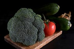 Fresh broccoli, zucchini and one tomato on a cutting board on a black background, rustic style, dark key royalty free stock image
