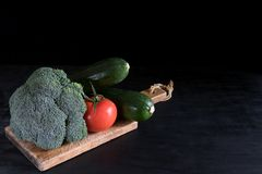 Fresh broccoli, zucchini and one tomato on a cutting board on a black background, rustic style, dark key stock images