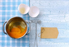 Fresh broken raw egg in pan. Whisk for whipping, paper tag on wooden table Stock Photos