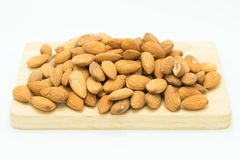 Fresh brown almonds seed on wooden board. On white background Royalty Free Stock Photos