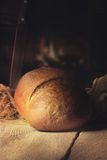 Fresh brown bread on a table in a warm kitchen Stock Photography