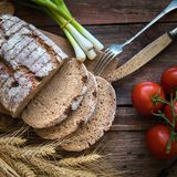 Fresh brown bread on a wooden plate with vegetables Royalty Free Stock Photos