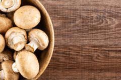 Fresh raw brown meadow on brown wood. Fresh brown champignons in a wooden bowl top view on brown wood background raw mushrooms Stock Photography