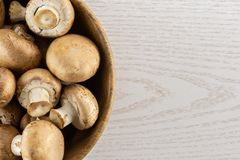 Fresh raw brown meadow on grey wood. Fresh brown champignons in a wooden bowl top view on grey wood background raw mushrooms Royalty Free Stock Images