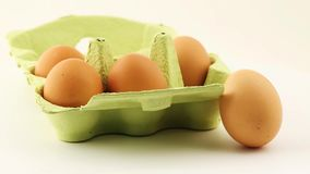 Fresh brown chicken eggs in and next to egg carton rotate on white stock footage