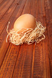 Fresh brown egg in straw nest on wooden background Royalty Free Stock Photo