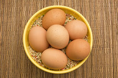 Fresh Brown Eggs. Uncooked brown eggs in a yellow bowl filled with raw bird seed on top of a bamboo place mat Royalty Free Stock Images