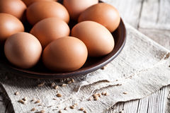 Fresh brown eggs in a bowl. Closeup on linen background Stock Image