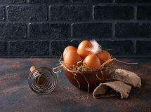 Fresh  brown eggs in bowl and whisk. Selective focus Royalty Free Stock Images