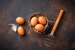 Fresh  brown eggs in bowl and whisk. Top view Royalty Free Stock Photo
