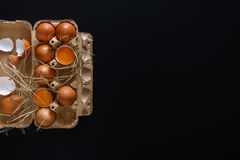 Fresh brown eggs in carton on black background Royalty Free Stock Photo