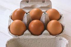 Fresh brown eggs in a carton. Six brown eggs in a carton on a white wooden table Royalty Free Stock Image