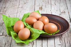 Fresh brown eggs in plate and green napkin Royalty Free Stock Images