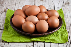 Fresh brown eggs in plate and green napkin. On rustic wooden background Royalty Free Stock Images