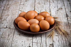 Fresh brown eggs in plate. And wheat ears on rustic wooden background Stock Image