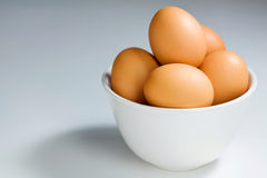Fresh Brown Eggs in White Bowl on Blue Grey. Brown eggs in simple setting Stock Photography
