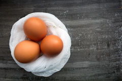 Fresh brown eggs. On a white cheesecloth on the dark wooden background. Easter concept Royalty Free Stock Photography