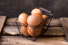 Fresh brown eggs in a wire basket on a vintage wood box, black background, Easter Royalty Free Stock Images