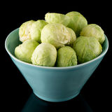 Fresh brussels sprouts. On blue ceramic bowl isolated on black background Royalty Free Stock Photos