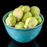 Fresh brussels sprouts. On blue ceramic bowl isolated on black background Stock Images
