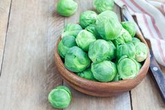 Fresh brussels sprouts in a bowl on wooden background, horizontal, copy space. Fresh brussels sprouts in bowl on wooden background, horizontal, copy space Stock Photos