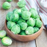 Fresh brussels sprouts in bowl on wooden background, square format. Fresh brussels sprouts in a bowl on wooden background, square format Stock Photography